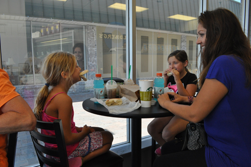 Rebecca Nyilas, 7, of Cutchogue has fun with her food Thursday while enjoying lunch with her friend CC Occhiogrosso of Mattituck, also 7, and CC's mom, Erin.