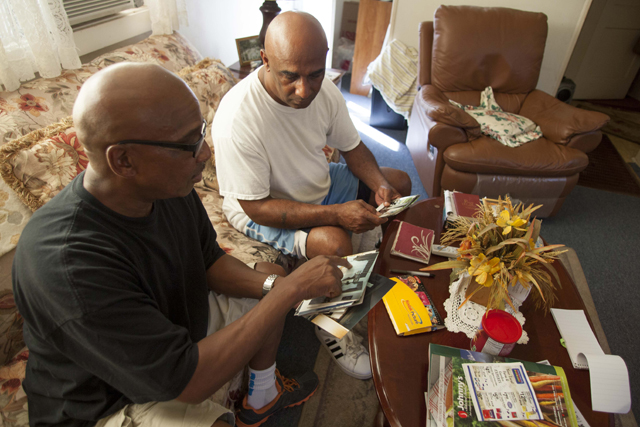 Malcolm (left) and Kevin Grigg look over pictures of their stepfather Monday. (Credit: Chris Lisinksi)