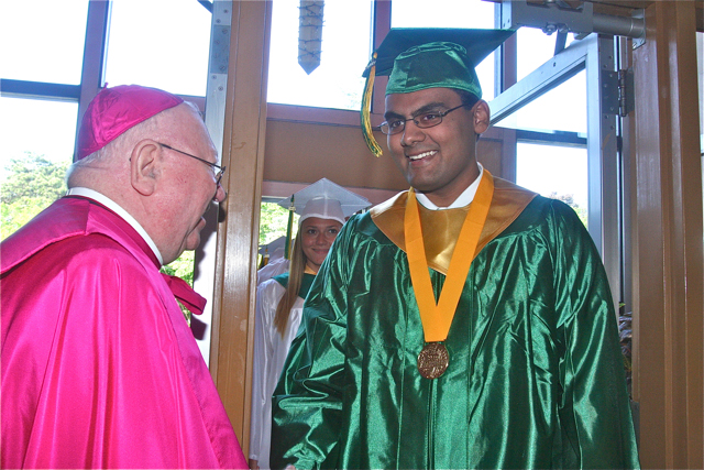 Valedictorian Elison Louis greets Bishop William Murphy. (Credit: Barbaraellen Koch)