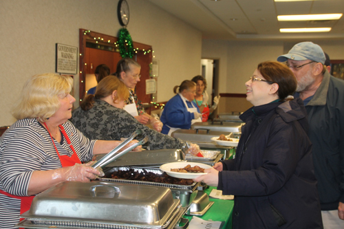 PAUL SQUIRE PHOTO | Volunteers serve up some sausage at Sunday's breakfast fundraiser.