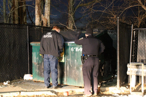 PAUL SQUIRE PHOTO | Riverhead authorities investigate the latest dumpster fire in Riverhead Sunday evening.