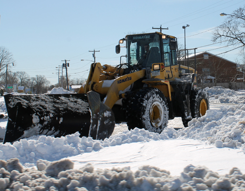 PAUL SQUIRE PHOTO | A bulldozer clears snow near the Flanders traffic circle Sunday morning.