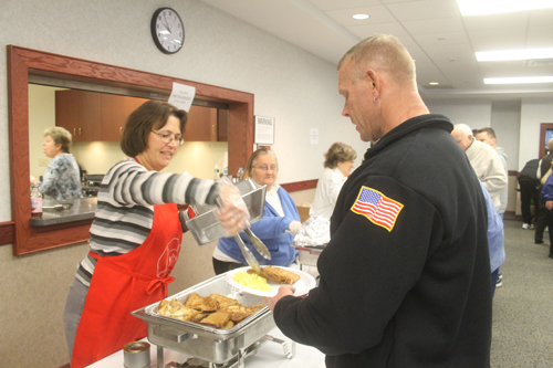 PAUL SQUIRE PHOTO | Barbara from the Ladies Auxiliary doles out french toast at Sunday's breakfast fundraiser.