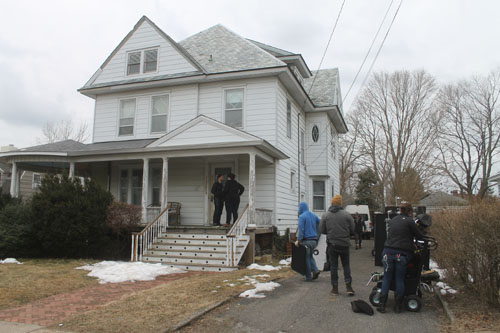 PAUL SQUIRE PHOTO | Film crews work a staging area outside an Ostrander Avenue home in Riverhead Tuesday morning.