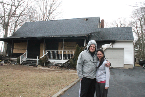 PAUL SQUIRE PHOTO | Brian and Shannon Schaller stand outside their ruined Aquebogue home Wednesday afternoon.