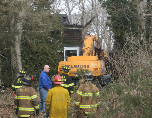 PAUL SQUIRE PHOTO | A Riverhead Highway Department vehicle begins demolishing the Aquebogue home destroyed in a fire Monday afternoon.