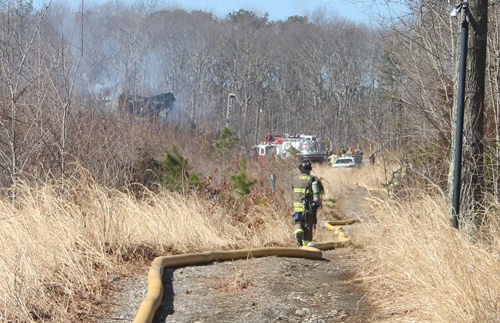PAUL SQUIRE PHOTO | An East Moriches firefighter walks towards the scene of a deadly house fire Wednesday morning.