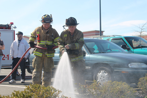 PAUL SQUIRE PHOTO | (R-L) Riverhead firefighters Skip Beale and Chris Schroer put out a mulch fire Sunday afternoon.
