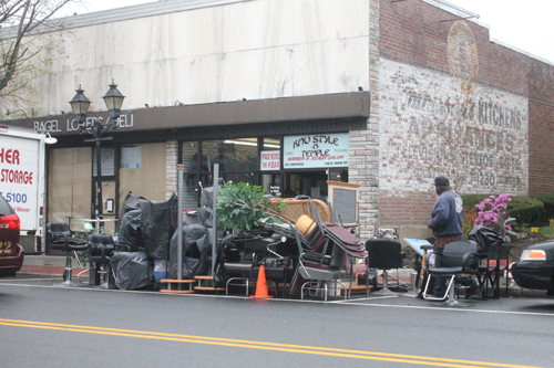 PAUL SQUIRE PHOTO | Workers clean out the Knu Style-N-Temple barber shop on East Main Street Tuesday morning.