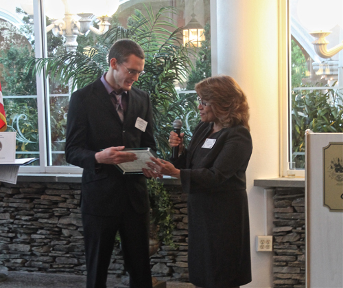 PAUL SQUIRE PHOTO | Jesse Hopkins receives his award from the Suffolk County HUman Rights Commission Thursday night.