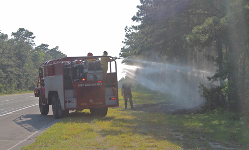 PAUL SQUIRE PHOTO | Riverhead firefighters douse the brush fires from a brush truck Thursday afternoon.