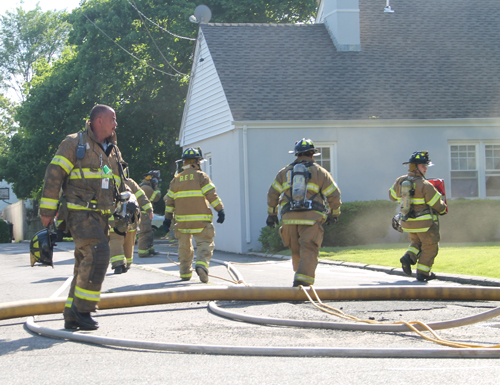 PAUL SQUIRE PHOTO   Riverhead firefighters prepare to clear out smoke inside a Riverhead home at the scene of a basement fire Wednesday evening.