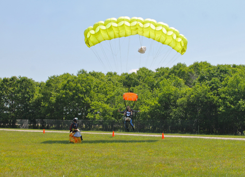 PAUL SQUIRE PHOTO | A skydiver lands in Calverton Sunday afternoon, where more than 40 people jumped out of planes to raise money for veterans mental health.