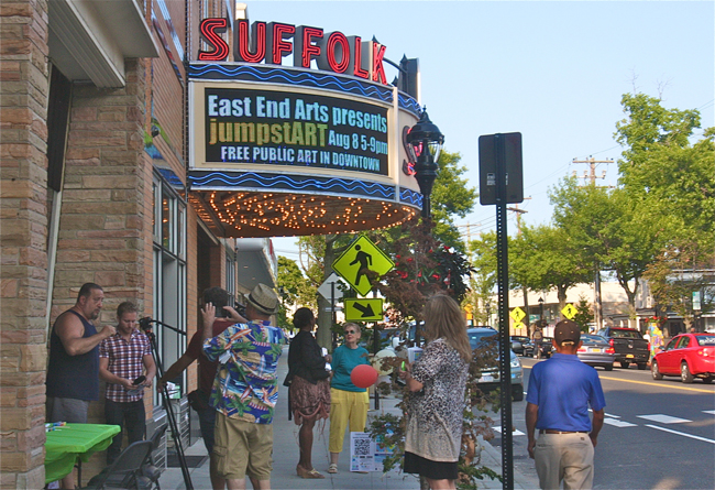 """Mixed media artist Charles Manfredi of East Islip (far left) is interviewed next to his diorama of his figures """"Baldies Visit Riverhead"""" by the Suffolk Theater Friday evening. (Credit: Barbaraellen Koch)"""