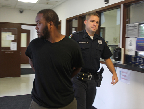 PAUL SQUIRE PHOTO | Leroy Jones III is led into his arraignment in Riverhead Town Justice Court Friday morning.