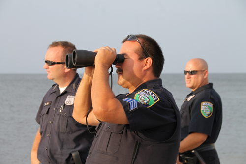 PAUL SQUIRE PHOTO | Riverhead police Sgt. John Vail (center) scans the ocean as Police Officers Christopher Parkin (left) and Rich Freeborn watch on.