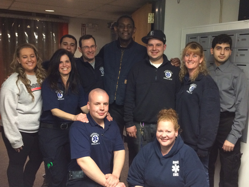 Lonnie Hughes (center, back row) stands with some of the EMTs who saved his life at Crazy Sports Night weeks ago. (Credit: Riverhead Volunteer Ambulance Corps)