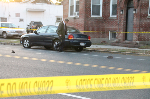 PAUL SQUIRE PHOTO | A Riverhead detective investigates the scene of the East Main Street car accident that seriously injured an elderly pedestrian Friday afternoon.