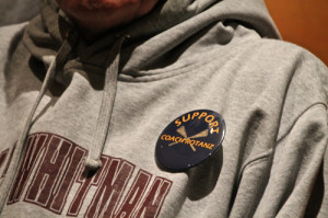 PAUL SQUIRE PHOTO | Students handed out buttons to help support their coach at the meeting.