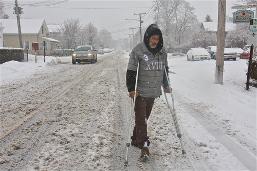 BARBARAELLEN KOCH PHOTO | Angel Almenis makes his way down Hamilton Avenue on crutches still recuperating from a broken ankle after he was hit by a car four months ago. He was headed to the Polish Town Corner Grocery and Deli to get coffee and breakfast.