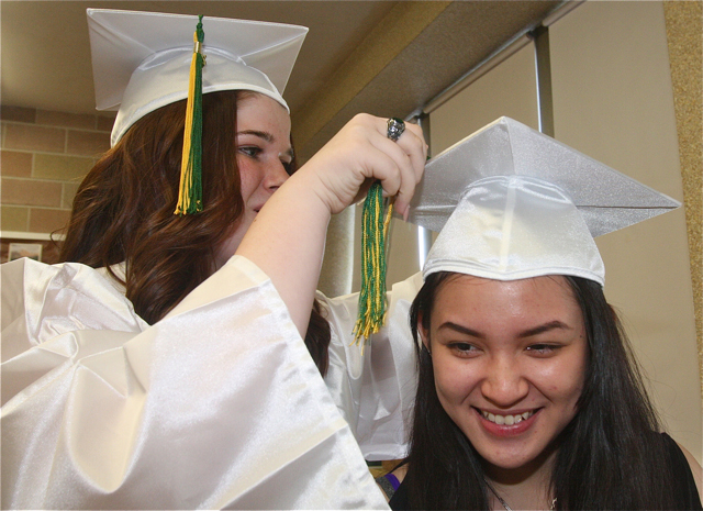 Jessica Marmelstein of Coram helps classmate City Le of MIller Place with her tassel. (Credit: Barbaraellen Koch)