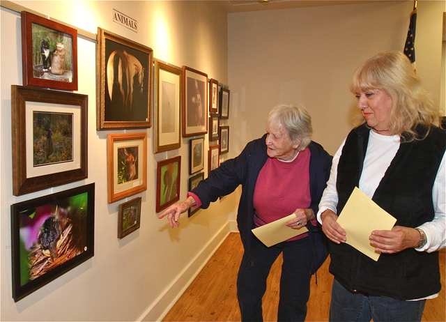 Roxie Shepish (left) and Theresa Gallo, both of Riverhead, admiring the animal photo entries. Ms. Shepish won a second place award in the abstractions/manipulations category. (Credit: Barbaraellen Koch)