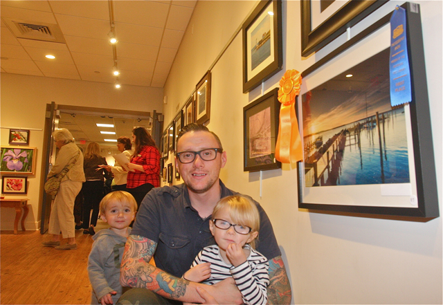 Jon Schusteritsch of Cutchogue posed with his children Max, 1 1/2, and Zoey, 4, by his photo chosen as the Friends Choice award for a landscape scene of docks and the bay at sunrise in New Suffolk. (Credit: Barbaraellen Koch)
