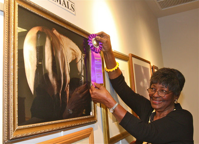 Friends of the Library Photo Show chairwoman Thelma Booker places the 'Best of Show' ribbon on Meghann Belser's portrait of a horse. (Credit: Barbaraellen Koch)