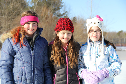 CARRIE MILLER PHOTO  |  At Stotzky Park's new ice rink Saturday, three friends from Baiting Hollow tried out their skating skills.