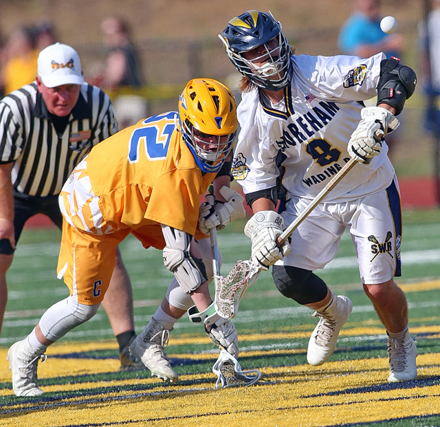 Shoreham-Wading River's Joe Miller (right) on the face-off for the WIldcats. (Credit: Garret Meade)