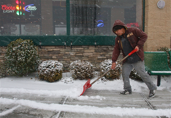 Luis Lopez cleaning off the sidewalk in front of Joe's Garage and Grill. (Credit: Barbaraellen Koch)