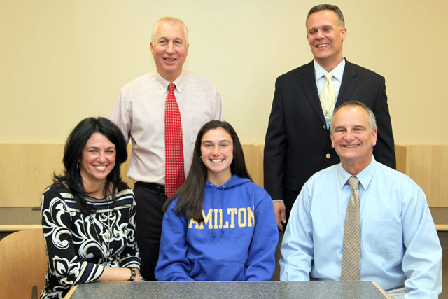 Riverhead senior Katie McKillop was joined be her parents Alice and Dave, as well as athletic director Bill Groth (standing, left) and high school principal Charles Regan for a signing ceremony. (Credit: Riverhead Schools)