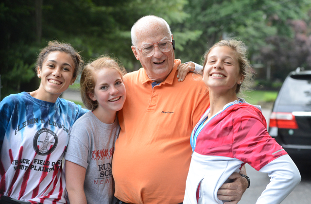 Coach Koretzki poses with three of his runners during the 2014 SWR July 4 5K race. (Credit: Robert O'Rourk)