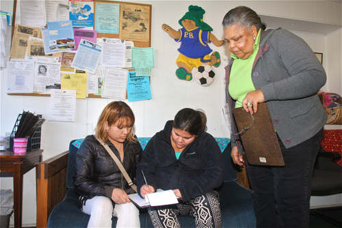 Sisters Yamileth and Maritza Carbajal, of Westhampton and Central Islip respectively, fill out paperwork for their monthly food allowance Friday afternoon as Long Island Council of Churches food pantry manager Carolyn Gumbs looks on. (Credit: Barbaraellen Koch photos)
