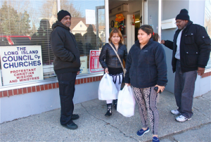 Yamileth and Maritza Carbajal leave LLIC Friday afternoon as clients Anthony Thomas (left) and Thomas Anderson, both of Riverhead, wait to go inside.