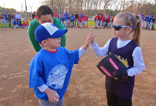Jonas Wan hi-fives Emma Freeborn, who threw out the first softbal pitch Friday. (Credit: Barbaraellen Koch)