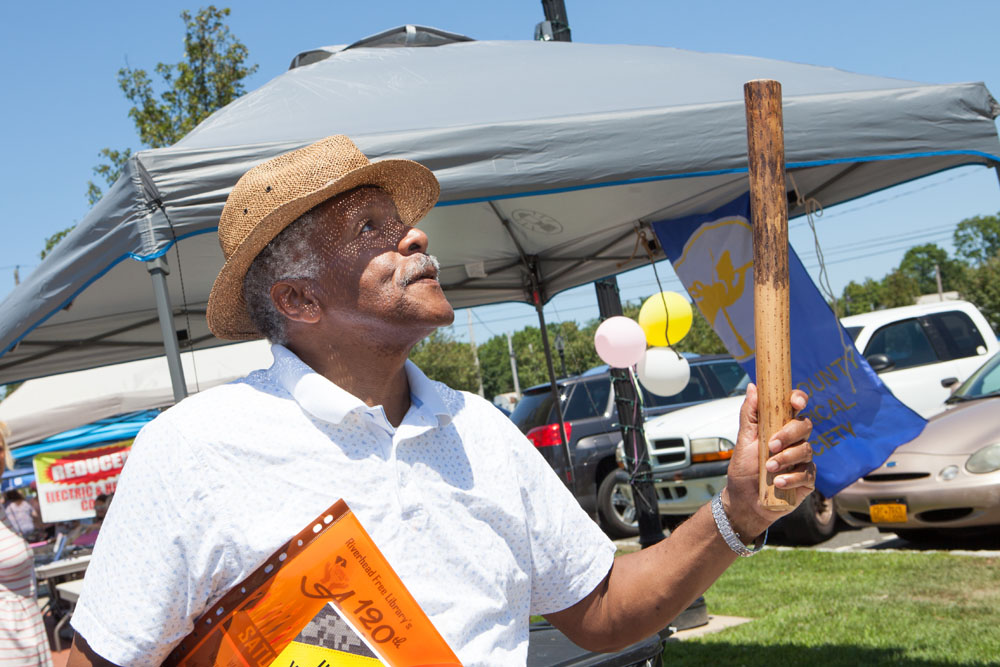 """Harry of Riverhead"" tries out a rain stick from a display provided by the Southold Indian Museum. (Credit: Katharine Schroeder)"
