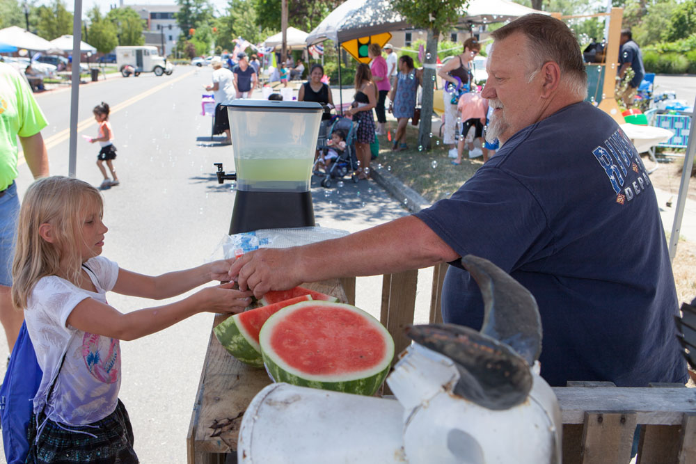 Peyton LaCombe, 9, of Riverhead accepts a slice of watermelon from Riverhead firefighter Joe Berezny. (Credit: Katharine Schroeder)