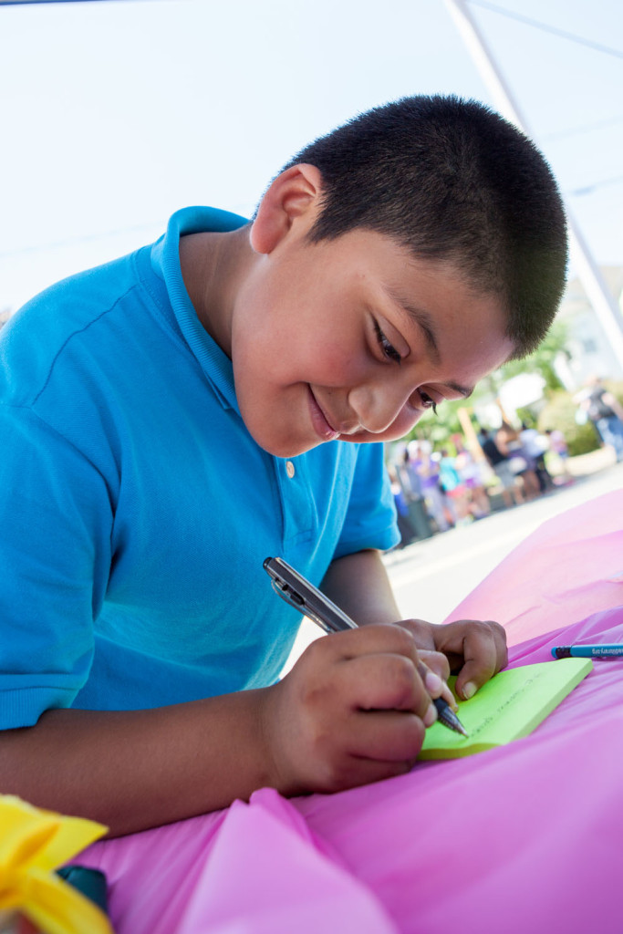 Jonathan Gochez, 10, of Riverhead writes a secret message to be placed in the time capsule. (Credit: Katharine Schroeder)