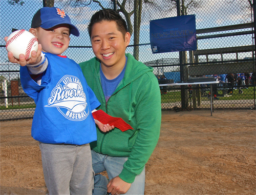 Jonas Wan, 4, at the opening ceremony for Riverhead Little League Friday evening, holding the ball and letter he donated to the league.