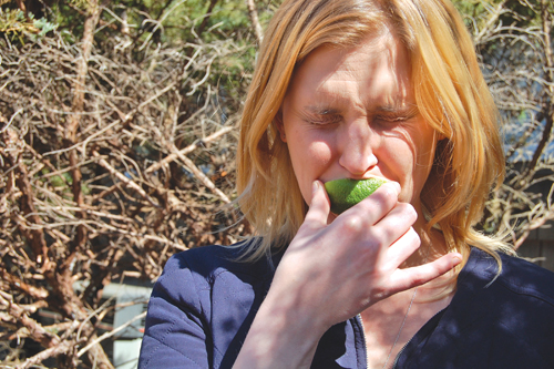 Reporter Cyndi Murray makes a sour face while biting into a lime outside the newsroom last Thursday. (Credit: Joseph Pinciaro)