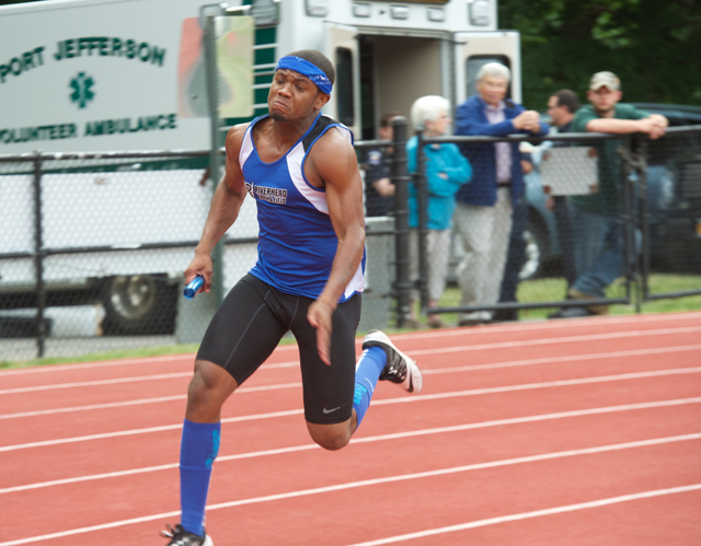 Riverhead junior Marcus Reid runs the third leg of the 4 x 100 relay Friday. The Blue Waves finished second Saturday but still earned a spot at the state meet. (Credit: Robert O'Rourk)