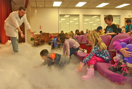 BARBARAELLEN KOCH PHOTO  |  Mad Scientist professor Will Hill fills the auditorium with CO2 gas 'fog' by dropping dry ice into buckets of hot water.