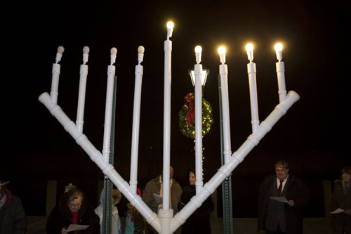 KATHARINE SCHROEDER PHOTO | Members of Temple Israel celebrate the menorah lighting at the Peconic Riverfront.