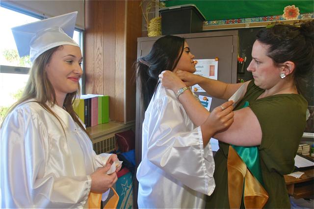 Art teacher Michele McLoughlin helps Kimberly Quiros (center) with her gown as Alexander Scharff waits. (Credit: Barbaraellen Koch)