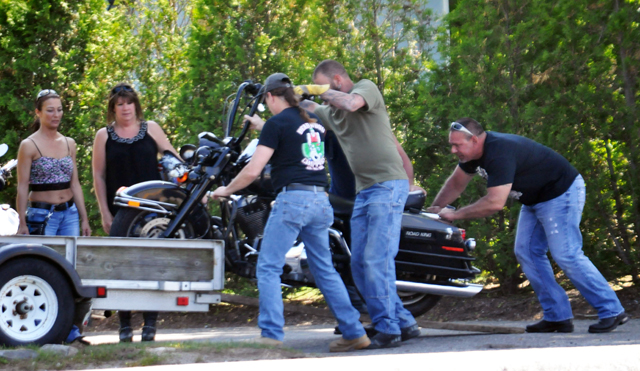 Friends load a motorcycle onto a trailer after a couple was injured riding on Sound Avenue in Calverton Sunday afternopon. (Credit: Grant Parpan)