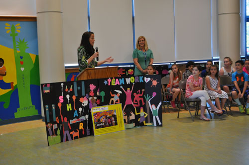Joyce Raimondo, left, and art teacher Melissa Haupt talk about the mural with students during Thursday's ceremony. (Credit: Rachel Young)