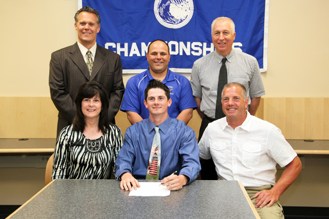 Riverhead senior Nick Herzog, pictured alongside his parents Debbie and Scott, will play baseball at the University of Massachusetts-Boston next year. High School principal Charles Regan (left), varsity coach Rob Maccone and athletic director Bill Groth joined them for a signing ceremony. (Credit: Riverhead School District)