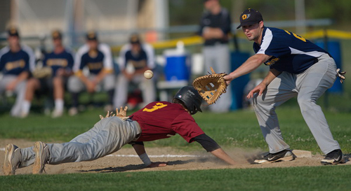 GARRET MEADE PHOTO | Riverhead's Michael; Brosseau dove safely back to the bag before North Fork first baseman Mike Hayden could slap a tag on him.