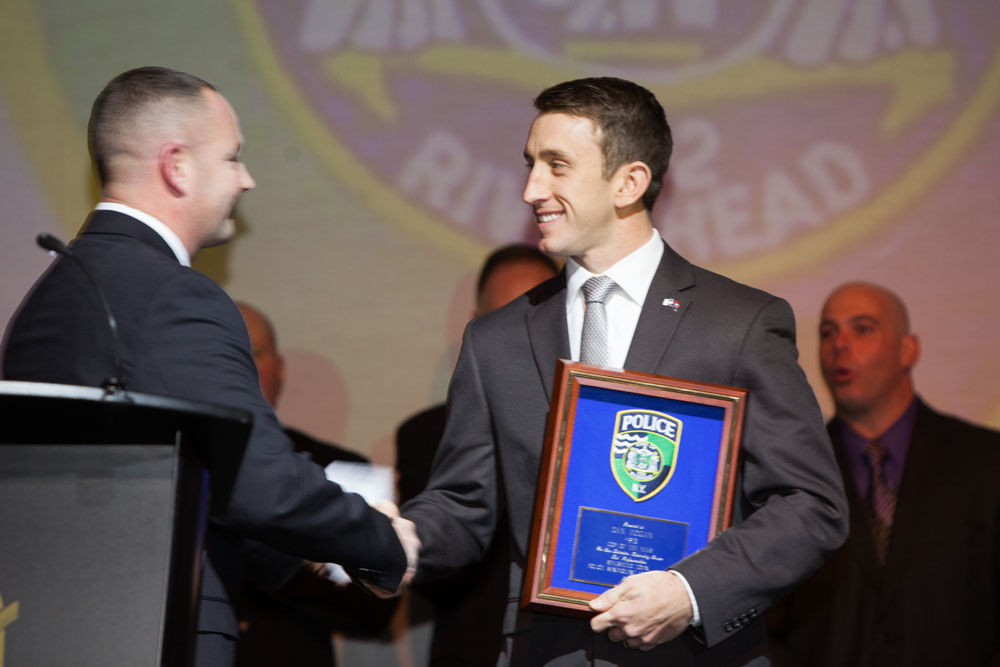 Officer John Morris presents the Cop of the Year award to Officer Daniel Hogan. (Credit: Katharine Schroeder)
